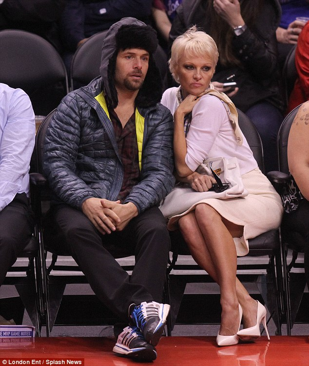 Turning up the heat: Pamela Anderson cuddled up to her husband Rick Salomon at a basketball game in Los Angeles on Wednesday