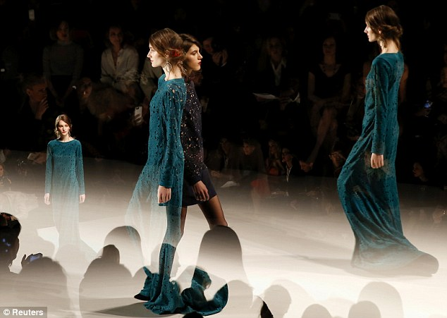 A great show: Models parade in forest green floor-length dresses and a black thigh-length frock