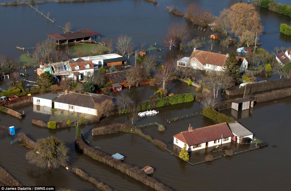 Homes: Lord Smith's visit to the flood-hit area came as Royal Marines were helping evacuate some 140 properties in the village of Moorland (pictured)