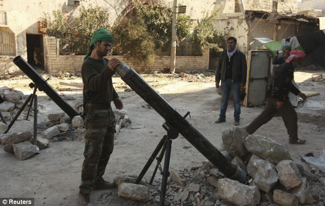 Ready to attack: Rebels have been besieging Aleppo prison for almost a year - having rammed suicide car bombs into the front gates twice. Above, a rebel fighter prepares to launch a mortar shell toward Assad's army
