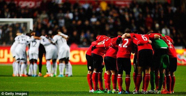 Final words: Players from both teams speak in a huddle ahead of kick-off