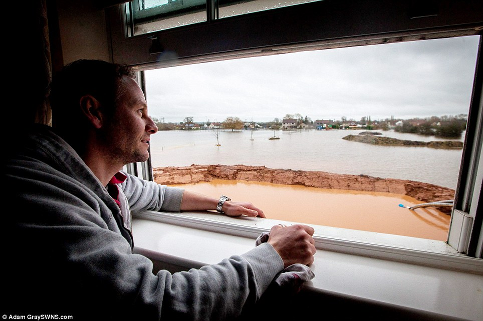 Sam Notaro, 40, looks out of his recently constructed £1 million house on the Somerset levels which he is desperately trying to protect