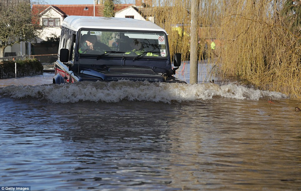 A Land Rover drives through flood waters in Moorland. The water has risen by so much it is almost level with the windshield