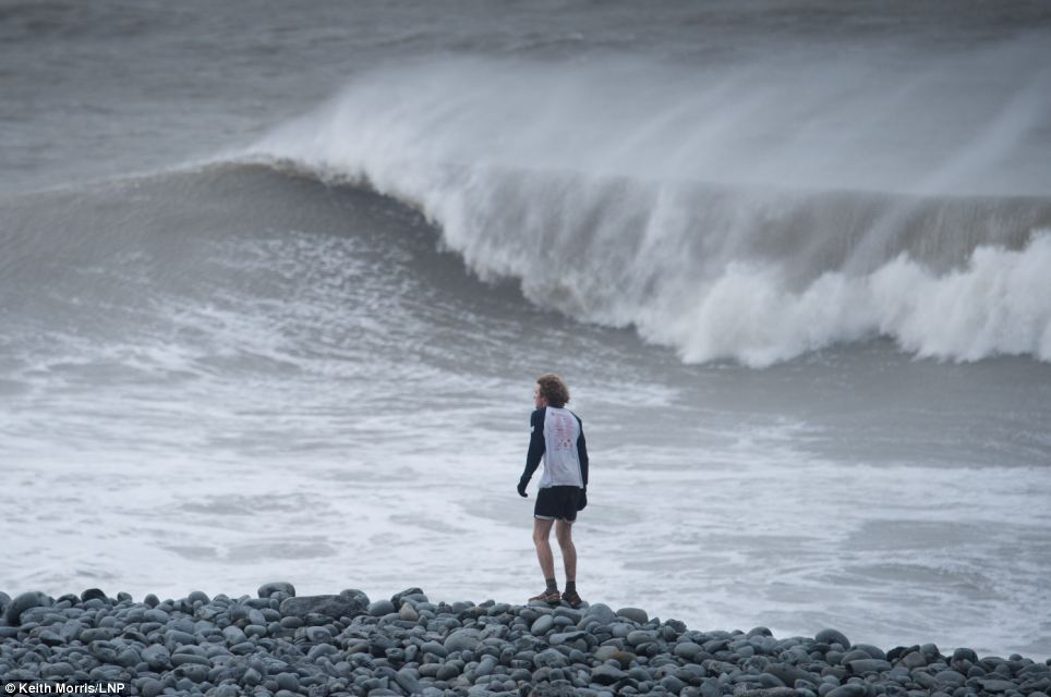 A runner watches gale force winds and big waves begin to strike the seafront at Aberystwyth on the west Wales coast