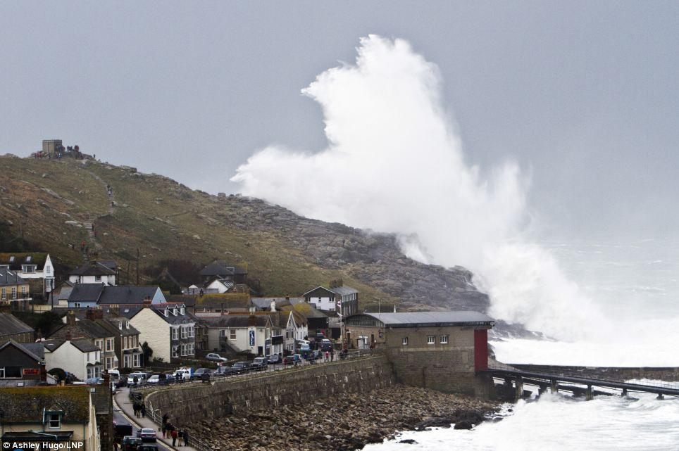 A wave bigger than Sennen Cove, in Cornwall, crashes over the cliffs as a series of devastating storms swept in bringing gales of up to 80mph
