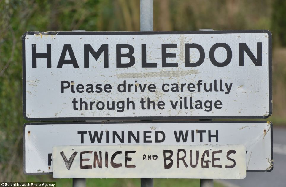 Residents in flood hit Hambledon, Hampshire, found time for a touch of humour - adding a make-shift sign stating the village is twinned with Venice and Bruges