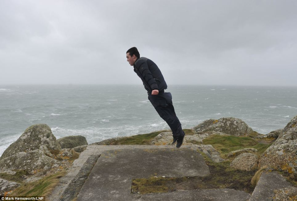 A man is lifted off the ground as gale force winds sweep up his jacket in Sennen Cove, Cornwall