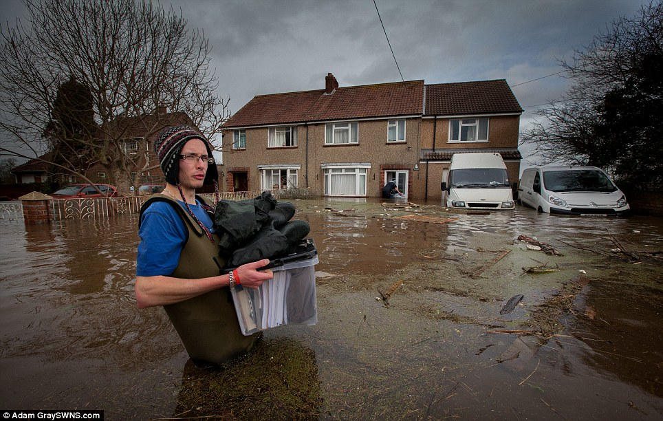 Darren Gwilliam helps a friend leave a flooded home in Moorland, Somerset. Flood waters have risen more than a foot over night and residents now believe the village will be completely lost to the water