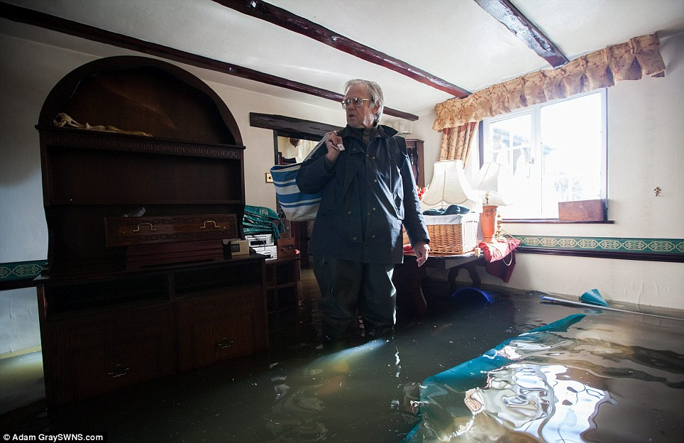 Phil Smithen, 63, leaves his flooded home in Moorland, Somerset. He is one of the last people to leave the village