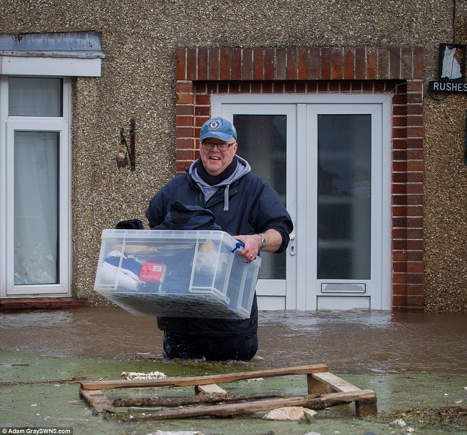 Paul Sayer, 58, leaves his flooded home after it is ravaged by a surge in the water levels overnight