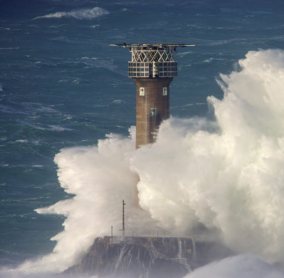 A spray from a wave reaches the top of the 35-metre high Longships Lighthouse at Lands End, Cornwall