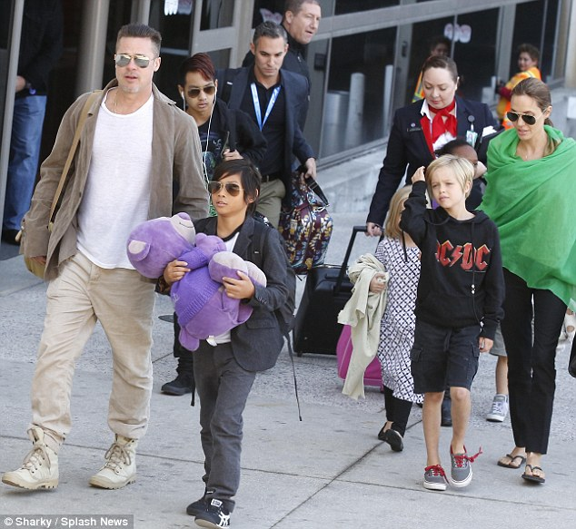Go to: The father-of-six wore a very similar pair of pants and boots when arriving at LAX on Feb. 2, 2014 with his partner Angelina Jolie and their brood