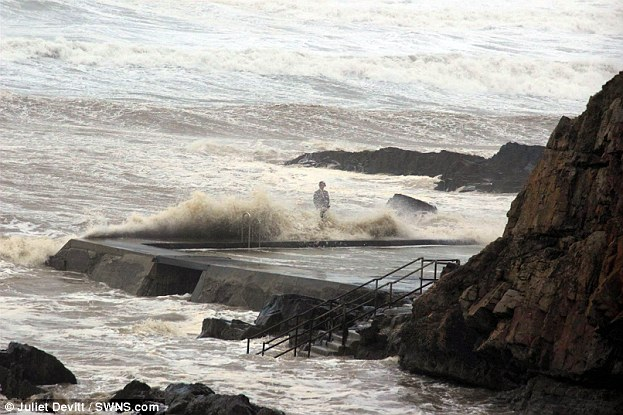 February 3: A man dressed in a suit risks his life by standing on the edge of a sea pool in Bude, Cornwall