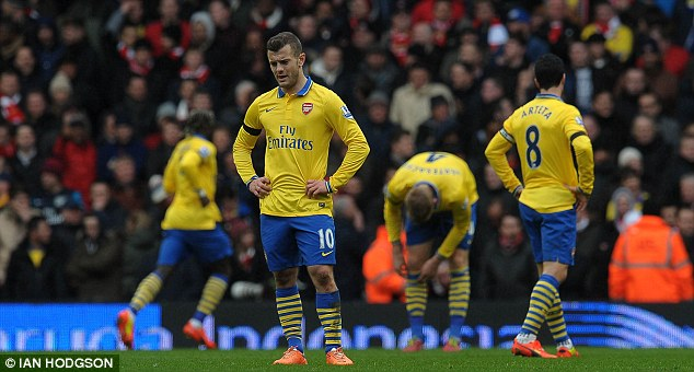 Down and out: Jack Wilshere (centre) looks at the ground in disbelief during Arsenal's defeat