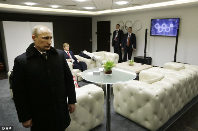 Vladimir Putin waits in the presidential lounge to be introduced at the opening ceremony of the 2014 Winter Olympics. Behind him, a TV screen shows four of the Olympic rings almost fully open at the start of the ceremony, while the fifth ring remains closed