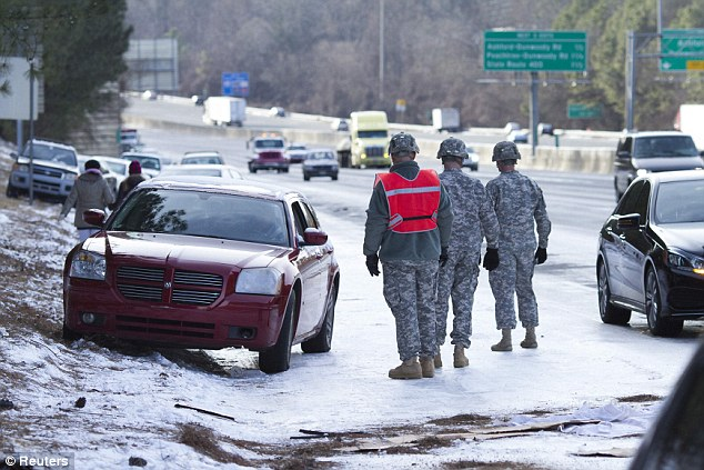 Unprepared: Georgia National Guard troops were called in to help people get their stranded cars out of the snow in Atlanta last month during a rare ice storm which turned the city into a slippery mess