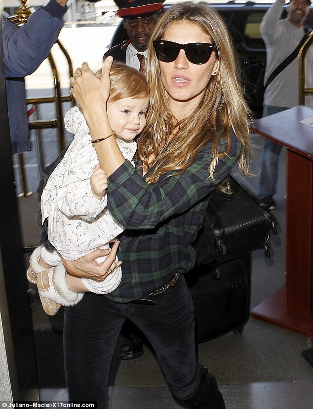 Protective: Gisele made sure her daughter was safe, covering her head as they headed through the airport
