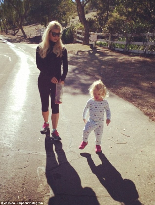 Her mini-me: Mother-of-two Jessica Simpson posted an adorable picture of her 21-month-old daughter Maxwell 'chasing shadows' while on a sunny stroll Monday