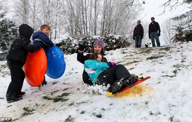 Making the most of it: Children sled down the hill at Madison Elementary School in Olympia, Washington