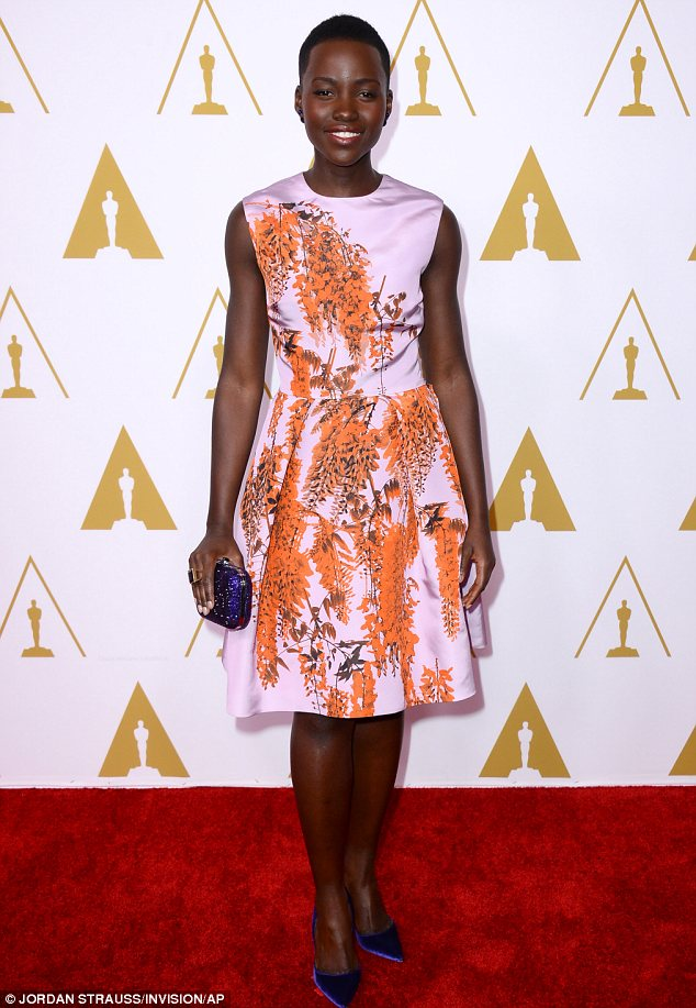 Red carpet darling: Lupita Nyong'o chose a demure orange printed dress for the event but jazzed it up with some bright purple accessories