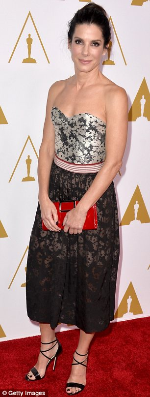 Petal power: Sandra Bullock wore a floral printed dress in dull tones with a different coloured top and skirt