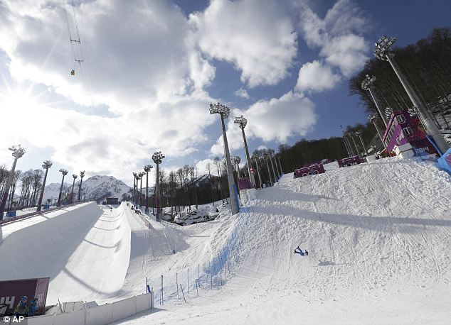 Long distance: A competitor crashes, right, during freestyle skiing aerials training at the Rosa Khutor Extreme Park on Monday