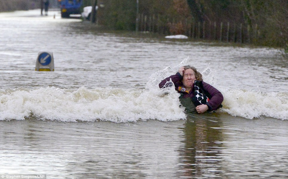 Swept away: A woman is hit by the wash from a lorry in Old Windsor after the River Thames burst its banks. The Environment Agency has issued 14 Severe Flood Warnings in the Thames area alone