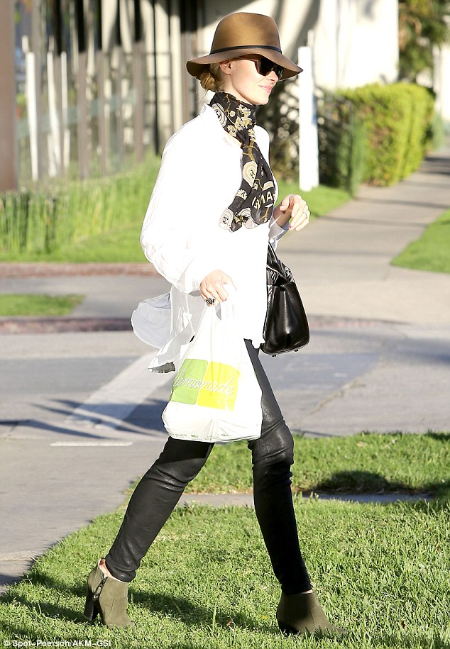 Effortless: She tied a black and gold scarf around her neck and carried a black patterned handbag