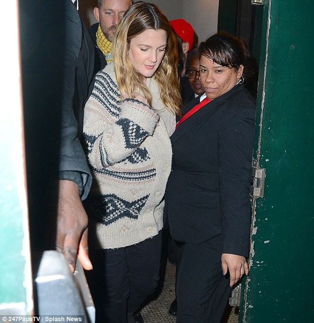 Tight squeeze: Drew struggled to get through the gap as the female security guard held open the rear door for her to exit