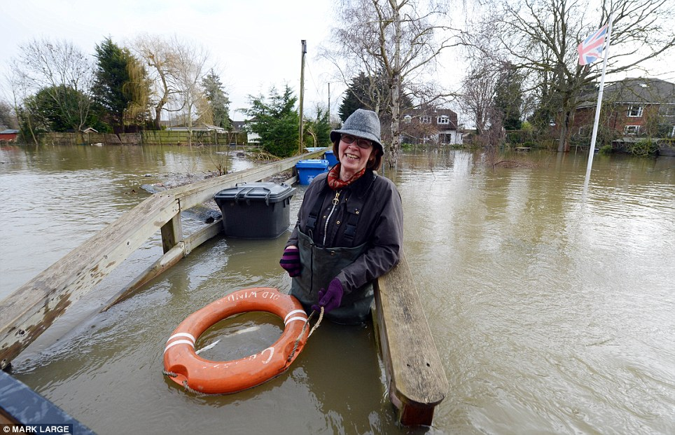 Getting across: Tricia Tompkins in chest-high waders on the bridge to cross to Friary Island, in Wraysbury, Berkshire