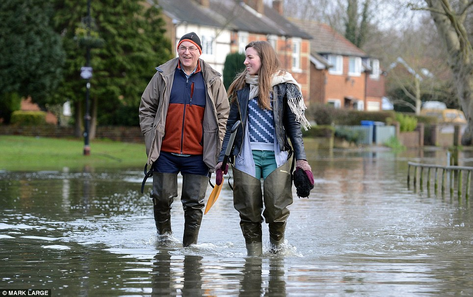 Staying positive: David and Emma Tompkins make their way through the streets in Wraysbury near Windsor, Berkshire