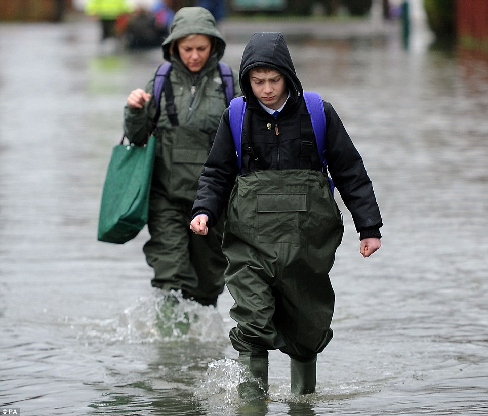 Unpleasant: Residents brave the flood water in Purley on Thames in Berkshire as they walk along a flooded street