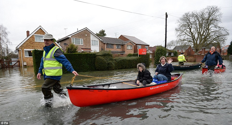 Waving: A local volunteer helps ferry local residents of Purley on Thames, Berkshire, up a flooded street