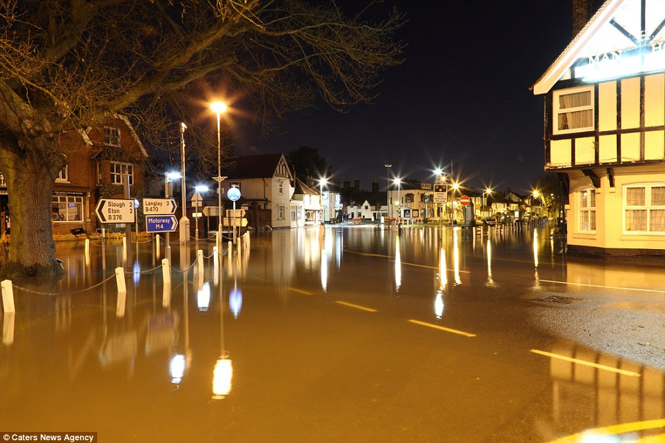 No traffic: Within hours, water rose around The Green at Datchet in Berkshire where homes and businesses were under immediate threat