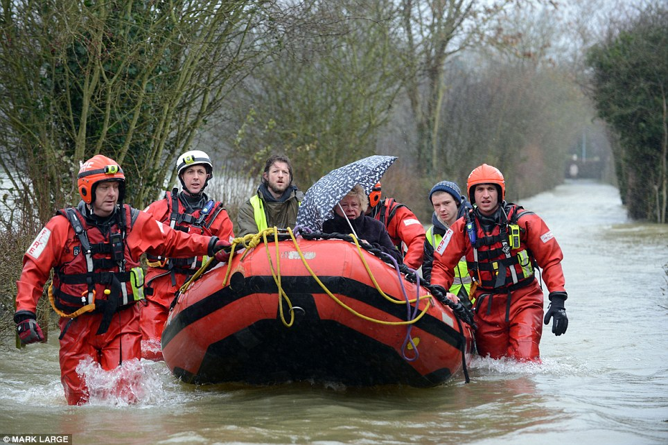 Under her umbrella: Joy Levinson, 75, is rescued with her dog by the fire brigade in Wraysbury, Berkshire