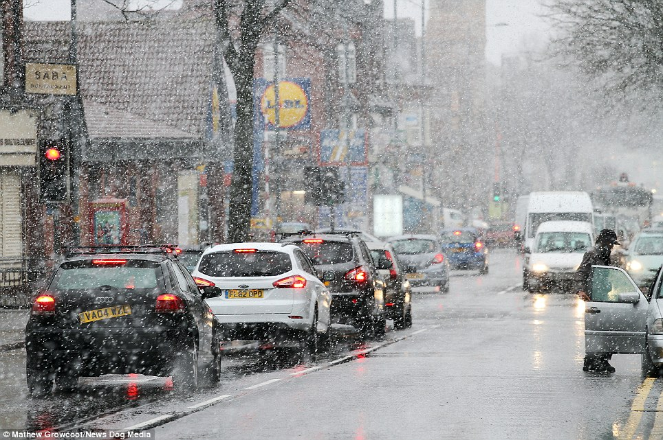 Elsewhere: Traffic struggles through snow in Balsall Heath, Birmingham, as flooding continues to devastate other parts of the country