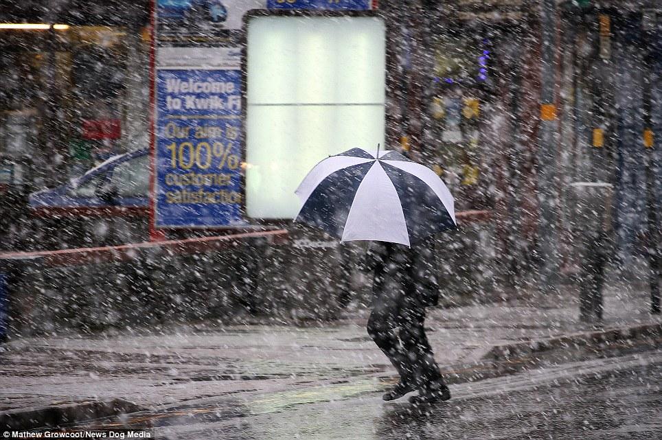 Carrying on: A man struggles with his umbrella through snow in Balsall Heath, Birmingham