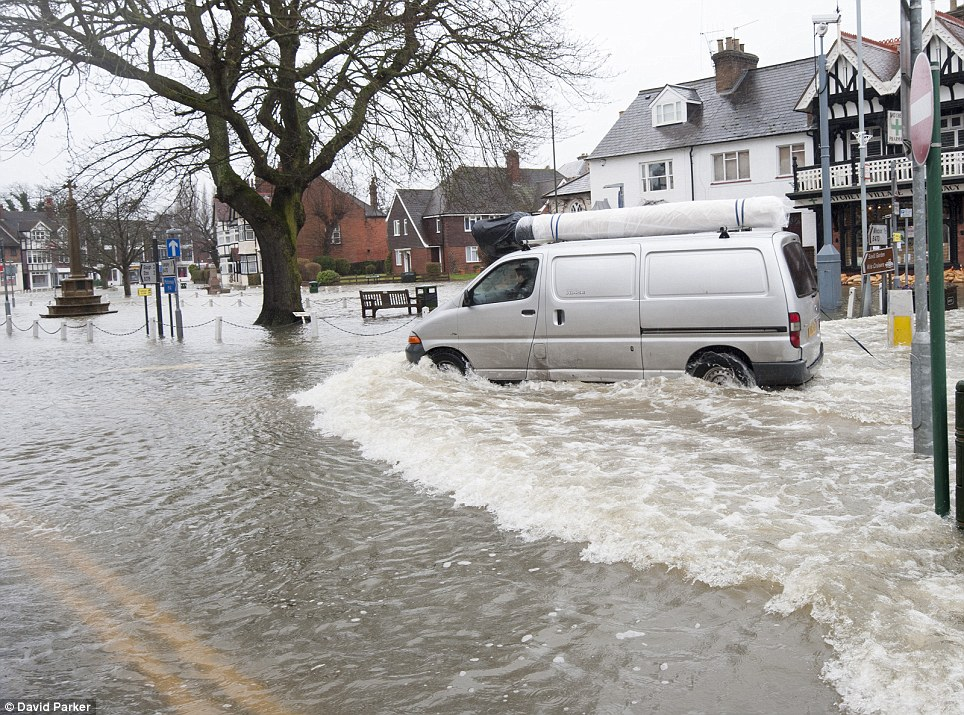 Motoring through: Residents of Datchet create a wash as they drive their vehicles at speed through the village, flooding the houses and shops