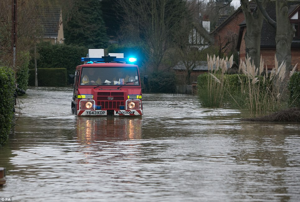 Adapted: Firefighters drive in a special vehicle through flooding in Wraysbury, Berkshire