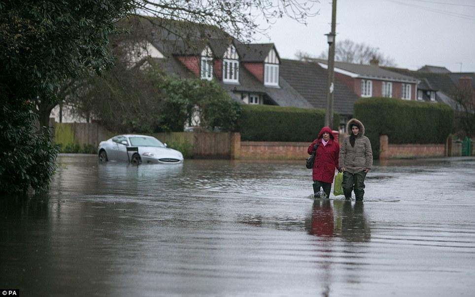 Wade in the water: Residents walk through floods in Wraysbury, Berkshire