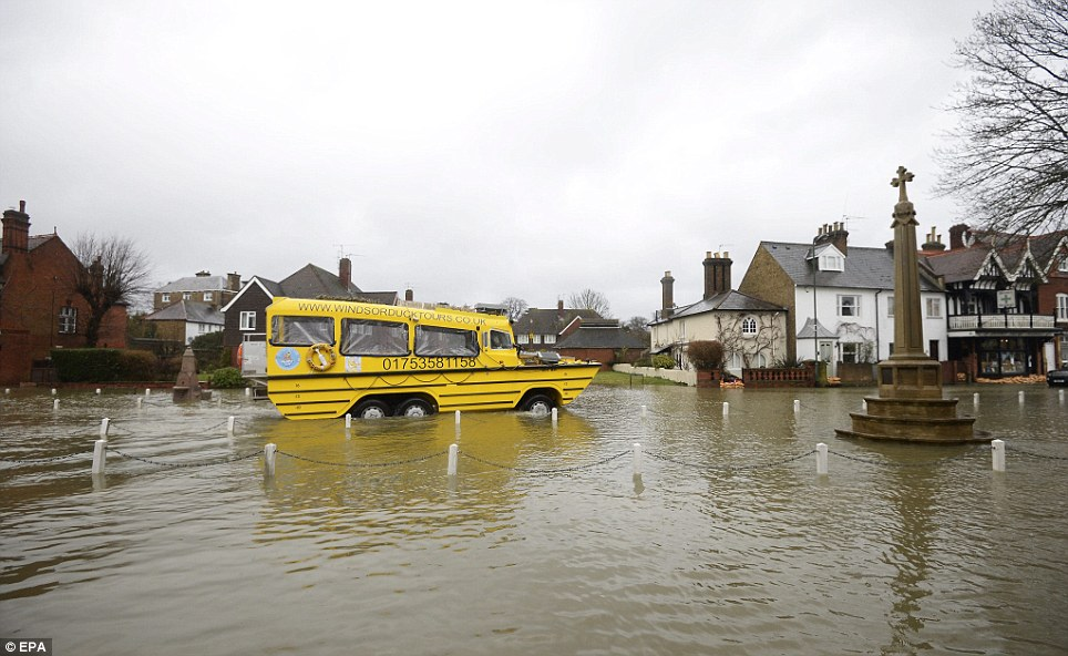 Helping out: A duck boat drives through flood waters in the Thames-side village of Datchet, Berkshire