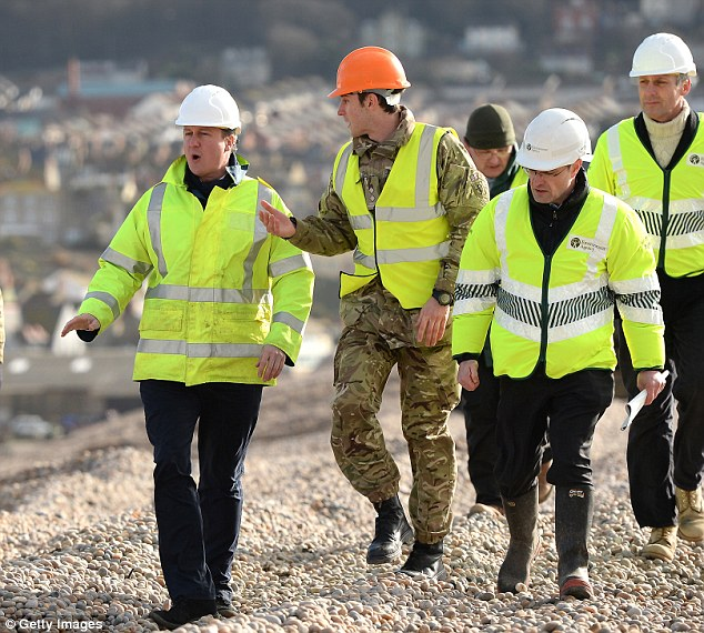 Photo op: Cameron meets members of the Environment Agency as he inspects work being carried out on Chesil beach between Portland and Weymouth in Dorset, yesterday