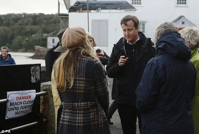 Prime Minister David Cameron speaks with residents whose homes were damaged during recent storms at Kingsand in Cornwall