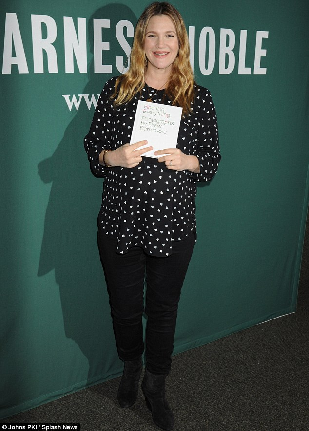 Showing off her baby: Drew looked delighted at the signing earlier in the evening as she posed up with her new book Find It In Everything