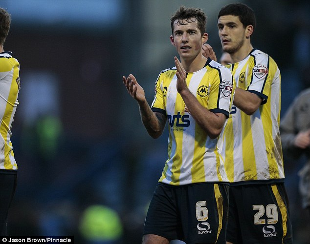 Hugh result: Torquay players Damon Lathrope (middle) and Anthony O'Connor (right) celebrate after their vital 1-0 win at Portsmouth on Saturday