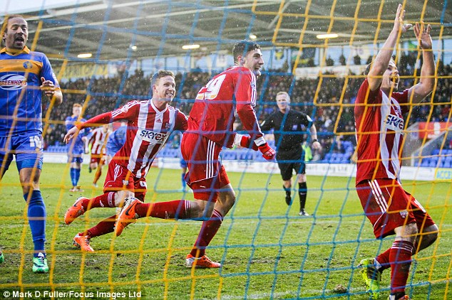 Bound for the Championship: Marcello Trotta celebrates after scoring Brentford's goal at Shrewsbury last time out - the match ended 1-1
