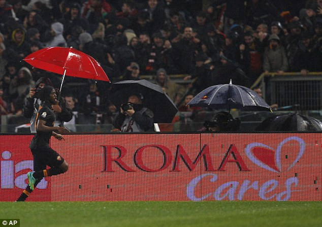 Singing in the rain: Gervinho celebrates after scoring the winner against Napoli in the first leg