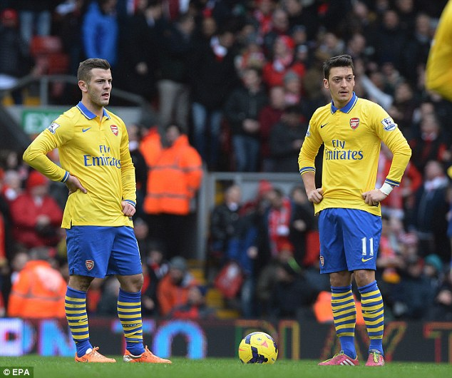 Bewildered: Jack Wilshere and Mesut Ozil look stunned as Liverpool take a 5-0 lead at Anfield on Saturday. The match ended 5-1