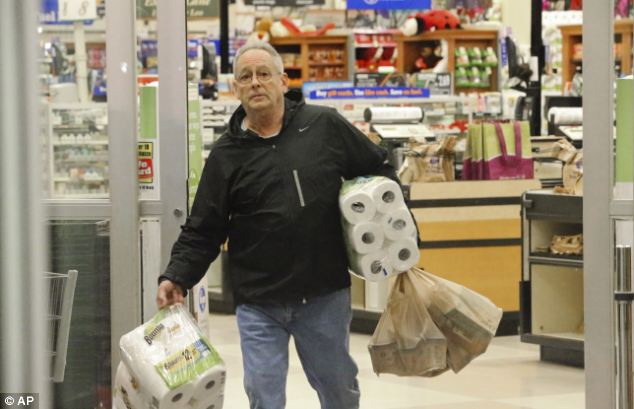 Getting ready: Richard Bethea leaves a store after stocking up on supplies on Monday in Atlanta ahead of a brutal winter storm which is expected to hit on Tuesday. Two weeks ago, the city was crippled by a snow storm