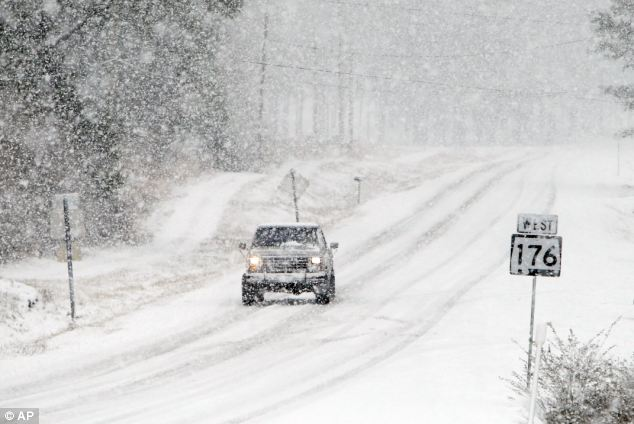 Snow-covered South: A truck slowly travels on Alabama highway 176 on Tuesday as 3 inches of snow fell